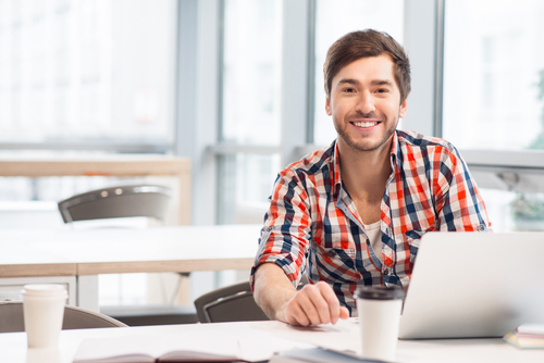 Man sitting at desk with laptop.