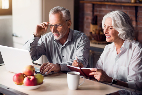 Older couple sitting at table looking at computer.