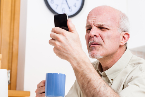 Elderly man with Presbyopia trying to read his cell phone