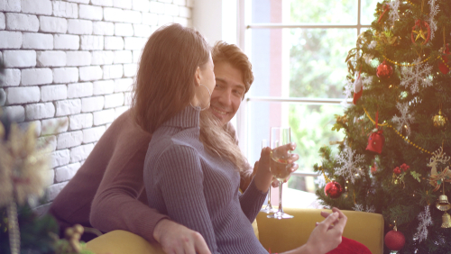 couple sitting by christmas tree with glasses of champagne